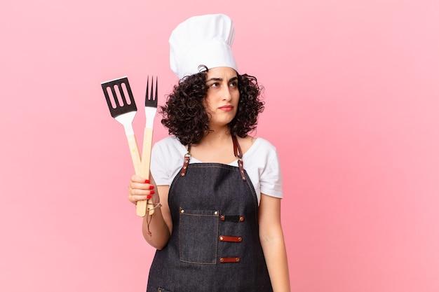 Hübsche arabische frau, die traurig, verärgert oder wütend ist und zur seite schaut. barbecue-koch-konzept