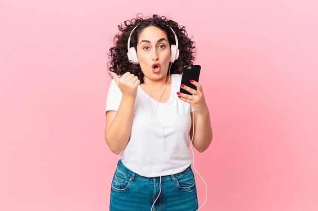 Hübsche arabische frau, die ungläubig mit kopfhörern und einem smartphone aussieht