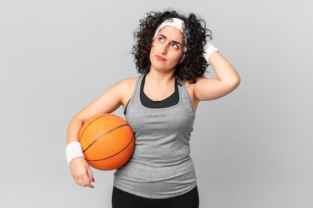 Hübsche arabische frau, die verwirrt und verwirrt ist, kopf kratzt und einen basketballball hält. sportkonzept