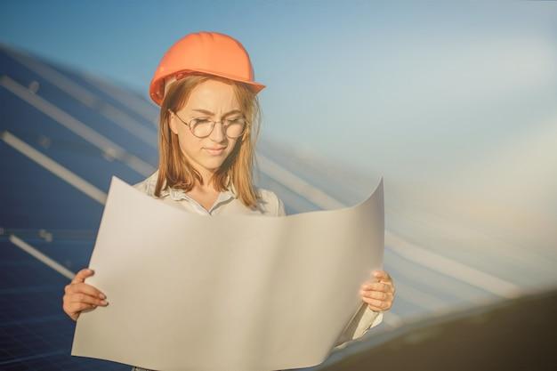 Hübsche architektin, die einen entwurf einer karte oder eines bauplanprojektplans untersucht