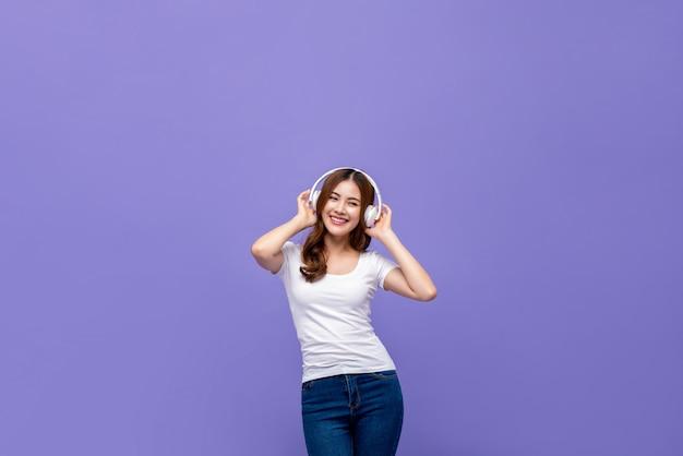 Hübsche asiatin, die musik auf kopfhörern tanzt und hört