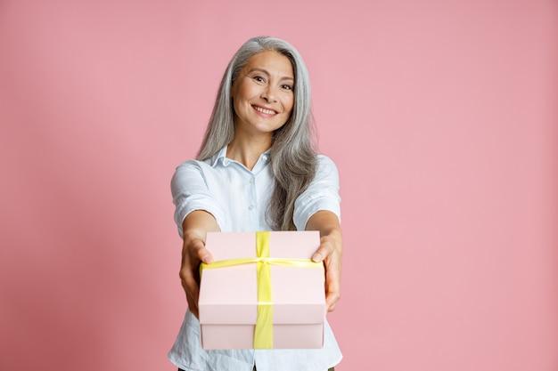 Hübsche asiatische dame mittleren alters mit langen, losen haaren präsentiert geschenk auf rosa hintergrund