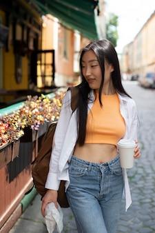 Hübsche asiatische frau, die an einem lokalen ort reist