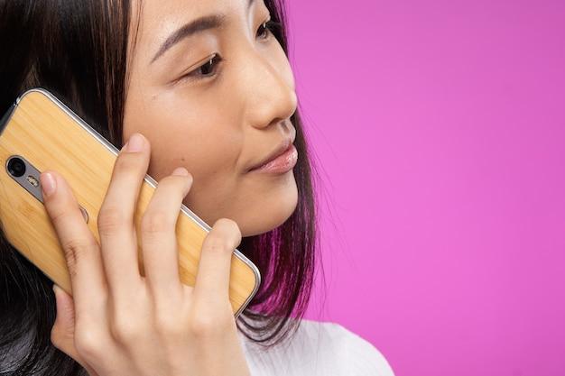 Hübsche asiatische frau, die auf der telefontechnologie-nahaufnahme spricht.