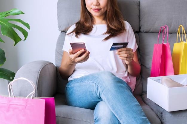 Hübsche asiatische frau, die auf sofa mit ihren modeartikeln des online-einkaufspakets sitzt und smartphone und kreditkarte hält. online-shopping-konzept.