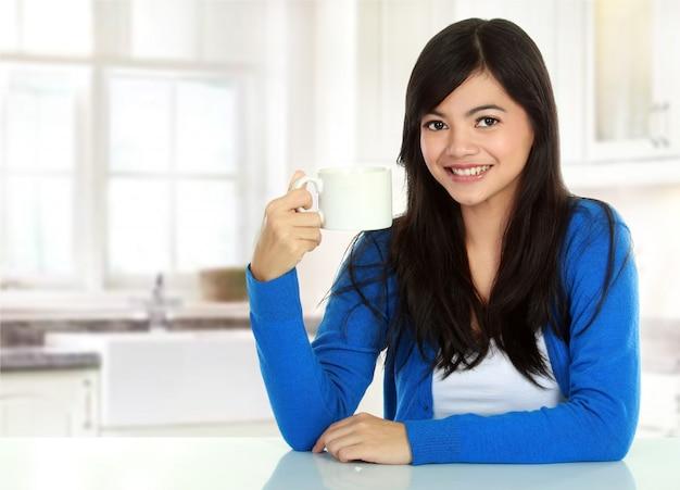 Hübsche asiatische frau, die ein glas tee trinkt
