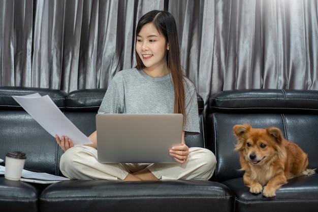 Hübsche asiatische frau, die entfernt von zu hause aus unter verwendung eines laptops arbeitet, der auf der couch oder auf dem sofa im wohnzimmer für die arbeit online mit haustierhündchen niedlichem hund und wächter, work-life-balance-konzept sitzt.