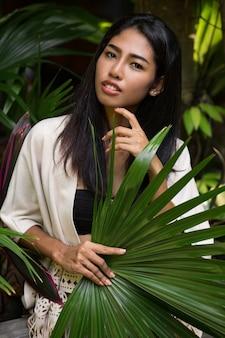 Hübsche asiatische frau, die im tropischen garten aufwirft, das großes palmblatt hält.