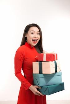 Hübsche asiatische frau in traditioneller kleidung, die geschenk für tet-feier hält