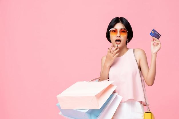 Hübsche asiatische frau mit den einkaufstaschen, die kreditkarte zeigen