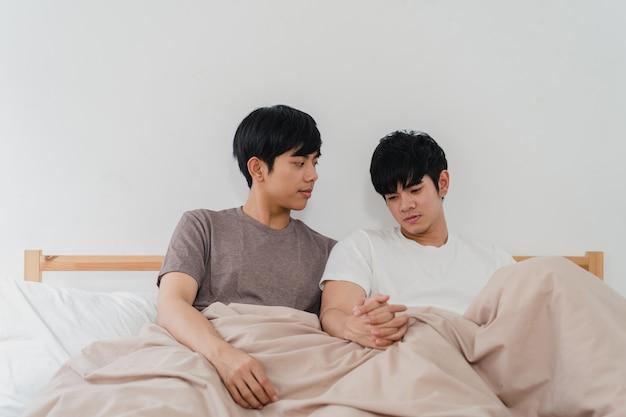 Hübsche asiatische homosexuelle paare, die zu hause auf bett sprechen. der junge asiatische glückliche lgbtq + kerl entspannen sich, verbringen zusammen romantische zeit, nachdem er morgens im schlafzimmer am modernen haus aufgewacht ist.
