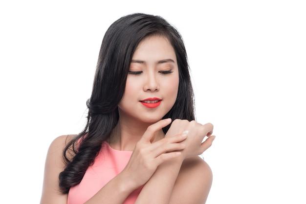 Hübsche asiatische junge frau, die creme auf ihre hand aufträgt