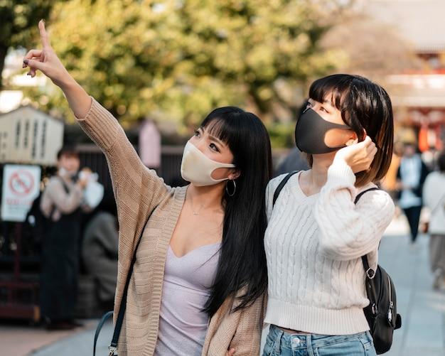 Hübsche asiatische mädchen, die gesichtsmasken tragen
