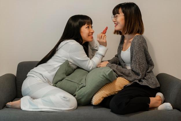 Hübsche asiatische mädchen, die make-up-produkte ausprobieren