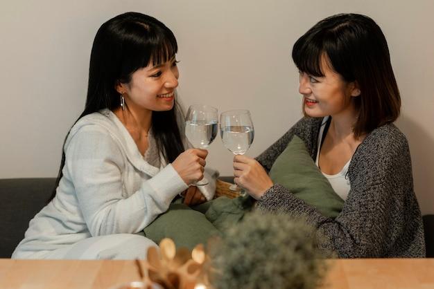 Hübsche asiatische mädchen, die wein zusammen genießen