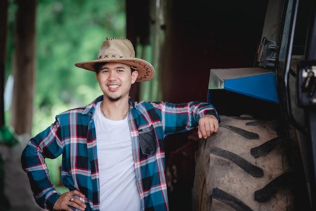 Hübsche asiatische männer, die lächelnde hemden neben traktoren für bauern tragen