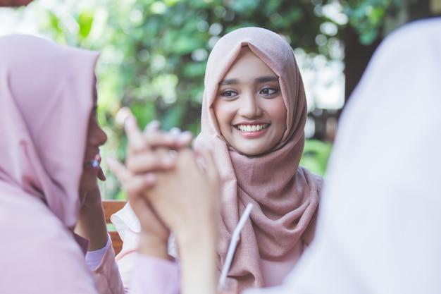 Hübsche asiatische muslimische frau, die spaß im café zusammen mit freunden hat