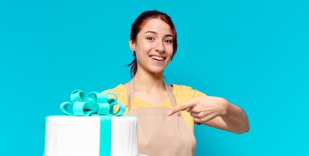 Hübsche bäckereiangestellte frau mit einer geburtstagstorte