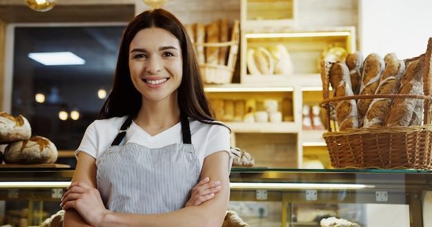 Hübsche bäckerin in gläsern, die auf dem tablet-computer scrollen und aufkleben, während sie an der theke im laden stehen. innen