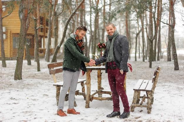 Hübsche bärtige männer, die an einem wintertag hände schütteln
