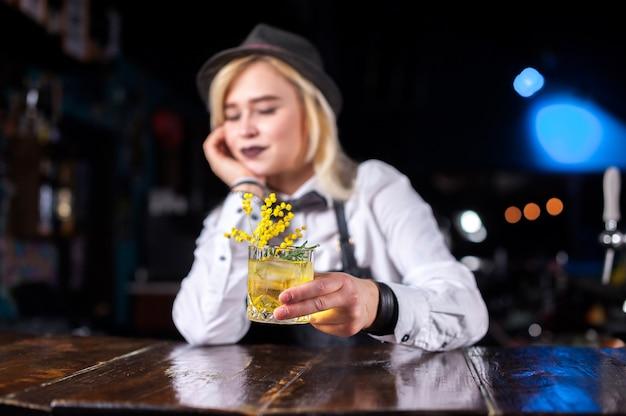Hübsche barkeeperin demonstriert den prozess der zubereitung eines cocktails, während sie in der nähe der bartheke in der bar steht