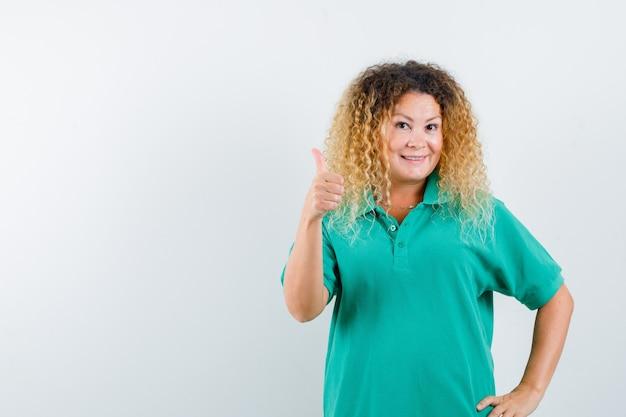 Hübsche blonde dame, die daumen oben im grünen polo-t-shirt zeigt und fröhlich aussieht. vorderansicht.