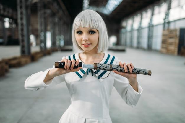Hübsche blonde dame im anime-stil mit schwert. cosplay mode, asiatische kultur, puppe mit klinge, süße frau mit make-up im fabrikladen