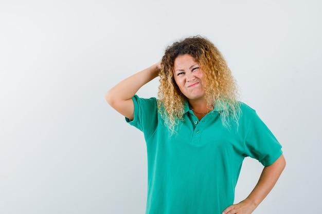 Hübsche blonde dame im grünen polo-t-shirt, das kopf kratzt, während sie ihr gesicht runzelt und vergesslich aussieht, vorderansicht.