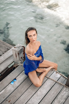 Hübsche blonde dame mit verführerischen augen, die blaue kleidung trägt, auf einer holzbrücke sitzt und posiert