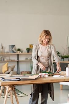 Hübsche blonde designerin in grauer, eleganter freizeitkleidung, die am holztisch im wohnzimmer steht und über kreative komposition arbeitet