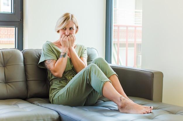 Hübsche blonde frau, die besorgt, ängstlich, gestresst und ängstlich aussieht, fingernägel beißt und zum seitlichen kopierraum schaut