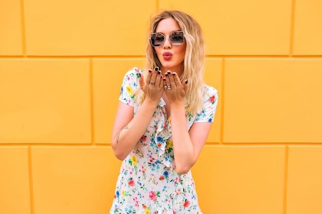 Hübsche blonde frau, die blumenkleid trägt und nahe gelber wand aufwirft