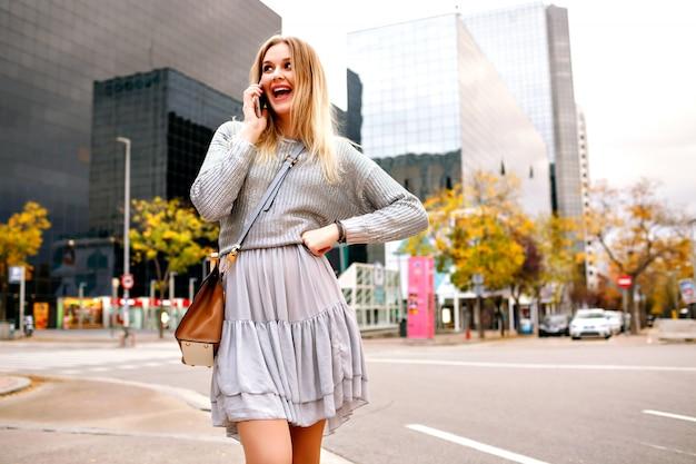Hübsche blonde frau, die durch ihr telefon auf der straße nahe städtischen gebäuden, grauem pullover und weiblichem rock spricht