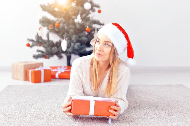 Hübsche blonde frau, die einen warmen strickpullover trägt und auf einem teppich in der nähe eines geschmückten weihnachtsbaums in einem wohnzimmer liegt. viele geschenke unter baum.