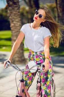 Hübsche blonde frau, die fahrrad fährt