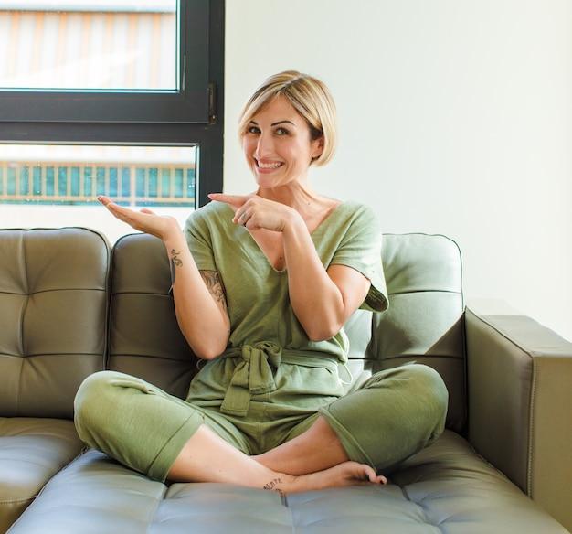Hübsche blonde frau, die fröhlich lächelt und zeigt, um raum auf handfläche auf der seite zu kopieren, ein objekt zeigend oder werbend