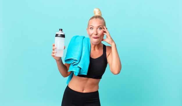 Hübsche blonde frau, die glücklich, erstaunt und überrascht aussieht. fitnesskonzept