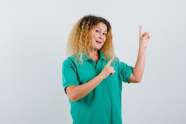 Hübsche blonde frau, die in grünem polo-t-shirt oben zeigt und erstaunt, vorderansicht schaut.