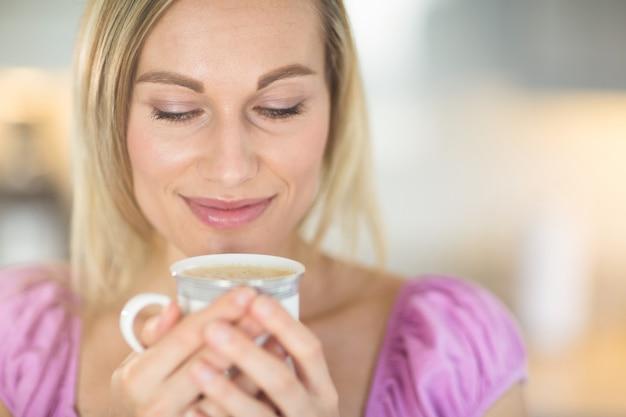 Hübsche blonde frau, die kaffee trinkt