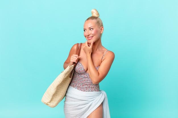 Hübsche blonde frau, die mit einem glücklichen, selbstbewussten ausdruck mit der hand am kinn lächelt. sommerkonzept