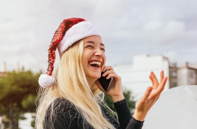 Hübsche blonde frau, die mit freund über handy für weihnachtstag spricht.