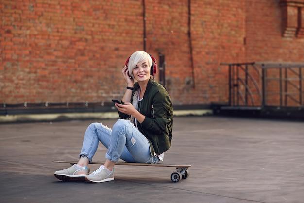 Hübsche blonde frau, die musik in den roten kopfhörern hört und telefon benutzt, während auf dem longboard an der backsteinmauer sitzt.
