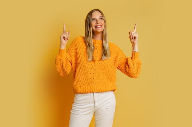 Hübsche blonde frau, die nach oben zeigt und lächelt, im orange stilvollen herbstpullover, der auf gelb aufwirft.