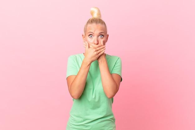 Hübsche blonde frau, die schockiert den mund mit den händen bedeckt