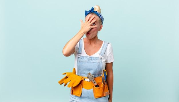 Hübsche blonde frau, die schockiert, verängstigt oder verängstigt aussieht, das gesicht mit der hand bedeckt und das hauskonzept repariert