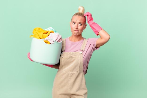 Hübsche blonde frau, die sich verwirrt und verwirrt fühlt und sich den kopf kratzt, wäschekonzept
