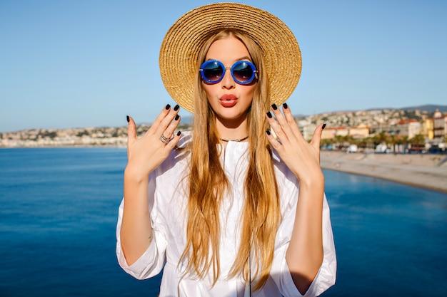 Hübsche blonde frau, die trendigen strohhut und blaue sonnenbrille trägt