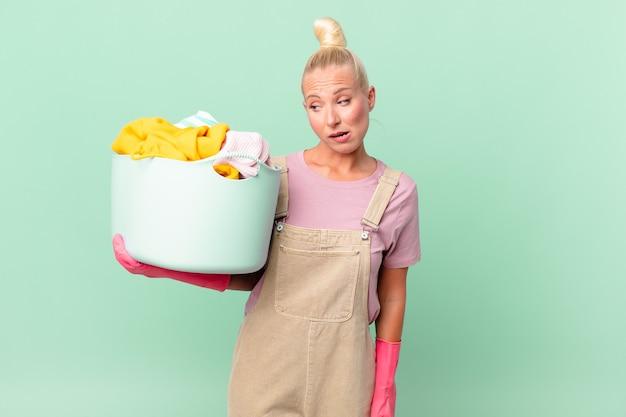 Hübsche blonde frau, die verwirrt und verwirrt das konzept der wäsche waschen fühlt