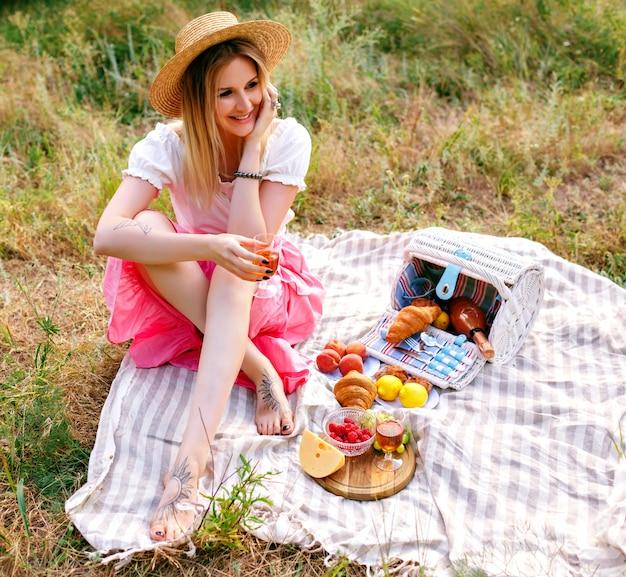 Hübsche blonde frau, die weinlesestil outfi trägt, landschaftspicknick genießt