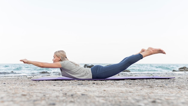 Hübsche blonde frau, die yoga im freien praktiziert